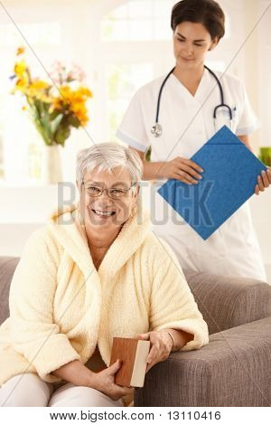 Happy elderly woman sitting on sofa at home, nurse watching from behind.?