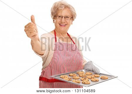 Mature lady holding a tray with chocolate chip cookies and giving a thumb up isolated on white background