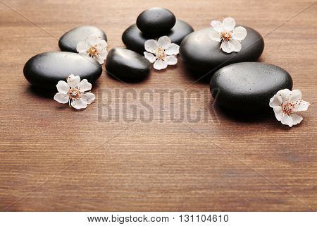 Heap of spa hot stones on wooden background