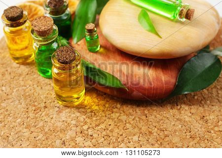 Bottles of tea oil on wooden background