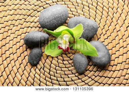 Spa stones and green orchid on a wicker mat, closeup