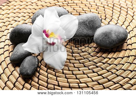 Spa stones and white orchid on a wicker mat, closeup