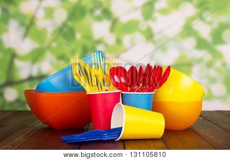 Bright plastic tableware: bowls, forks, spoons and cups on abstract green background.