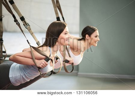 Pretty young women are training their arm muscles in gym. They are doing push ups while using trx straps. The girls are smiling with joy