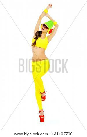 Full length portrait of a trendy DJ girl in bright colorful clothes, sunglasses and headphones. Party style. Fashion studio shot. Isolated over white.
