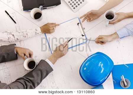 Businessmeeting, closeup hands of architects pointing at clipboard on office table.?