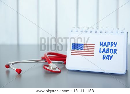 Notebook with printed text HAPPY LABOR DAY and stethoscope on wooden background