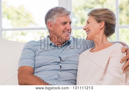Portrait of smiling happy senior couple sitting at home. Senior couple relaxing at home and looking at each other with affection. Cheerful older couple enjoying after retirement.