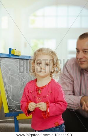 Smiling dad watching small daughter drawing on board at home.?