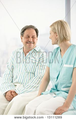 Senior patient in hospital, sitting on bed, chatting to nurse.
