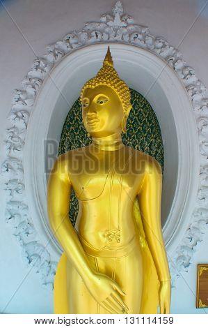 standing Buddha draped with an orange sash in an arcaded niche at Wat Phra Pathom Chedi