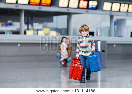 Adorable little kid boy with red and blue suitcases on international airport. Mother and daughter on background, happy family wating for flight and going on vacations.