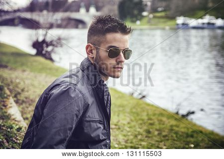Three-quarter length of contemplative light brown haired young man wearing grey jacket and denim jeans sitting on wall beside picturesque river in Turin, Italy