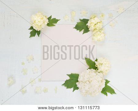 Scrapbooking page of wedding or family photo album frame with fresh white flowers and green leaves on light wooden background; top view flat lay overhead view