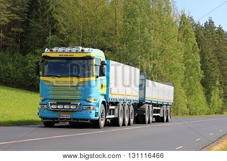 SALO, FINLAND - MAY 20, 2016: New customized Scania Euro 6 truck and open box trailer moves along rural road in South of Finland at spring.