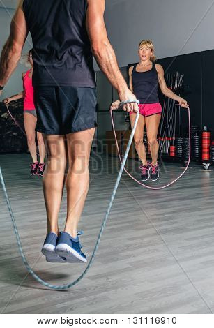 Back view of unrecognizable trainer teaching exercises with jumping ropes to women in a fitness class
