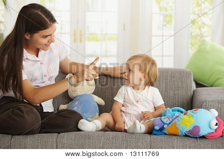 Mother teaching babygirl sitting on sofa at home, smiling.? poster