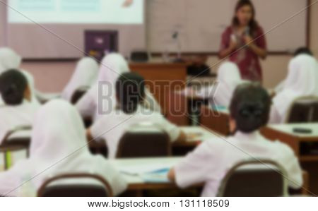 Blurred abstract background of university students sitting in a lecture room with teacher in front of the class with white projector slide screen: Blurry view from back of the classroom: Teachers day
