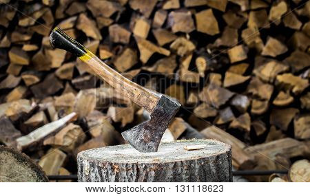 the old axe stuck in a stump on a background of chopped firewood poster