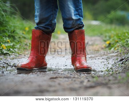 child's feet in the muddy, wet jeans and rubber boots. The child is in the pool