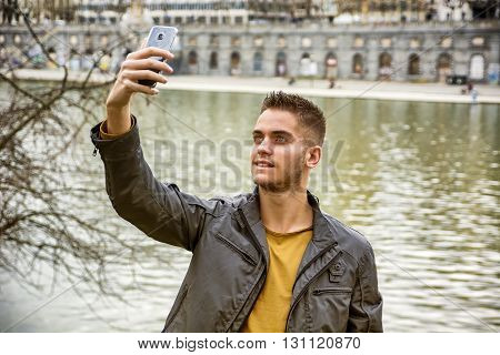 Three-quarter length of light brown haired young man wearing grey jacket and denim jeans taking selfie photo with his smartphone in front of picturesque river in Turin, Italy