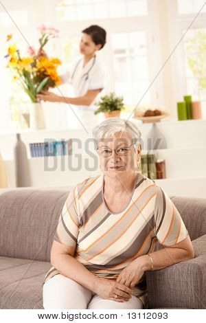 Portrait of happy senior woman sitting on sofa at home, nurse arranging flowers in background.?
