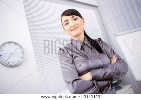Portrait of young businesswoman standing with arms crossed in office, lloking at camera, smiling. Low-angle shot.