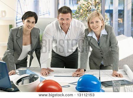 사무실 작업 계획, 카메라를 보고 서 있는 팀 건축가 웃 고?
