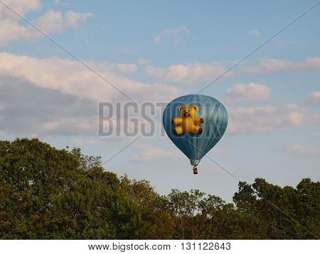 ELLICOTT CITY, MARYLAND - MAY 19 2016: A blue hot air balloon featuring a three dimensional teddy bear floats in the sky above Howard County in Maryland during the annual Preakness Celebration Hot Air Balloon Festival.