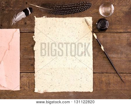Paper and quill pen on wood table
