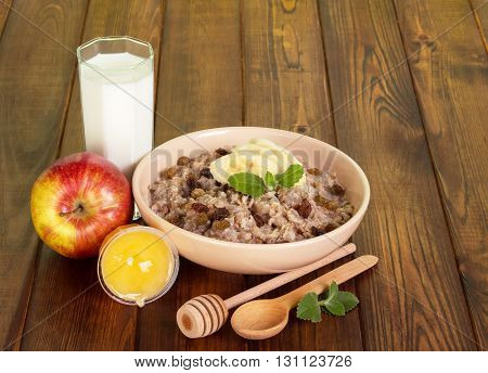 Healthy breakfast - a bowl of oatmeal with raisins and a banana, milk, honey and apple on background of dark wood.