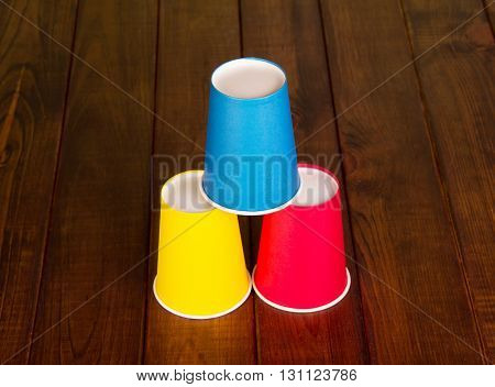 Pyramid from multi-colored disposable cups on the background of dark wood.
