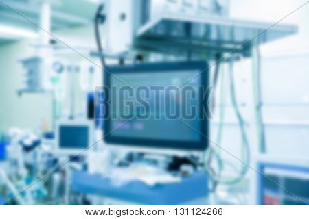 Abstract blurry medical background with functional vital signs monitor in operating room with machines in the background during real surgery. Life sustaining monitoring and anesthesia concept.