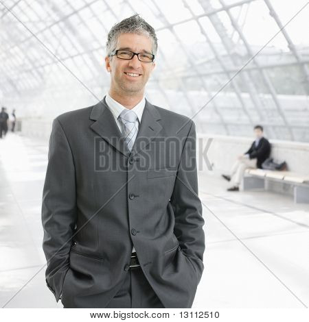Portrait of happy businessman standing with hands in pocket in office lobby, smiling.?