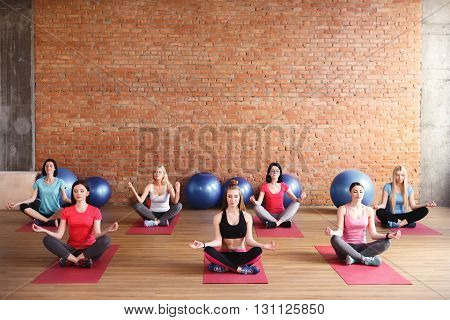 Attractive young women are meditating in gym. They are sitting in lotus positing and relaxing. Their eyes are closed with enjoyment