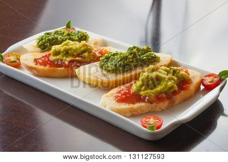 Ante pasto Guacamole with toast over a wooden table