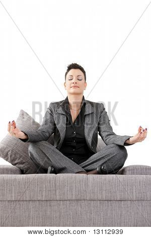Young businesswoman sitting on sofa relaxing in yoga meditation pose. Isolated on white background.?