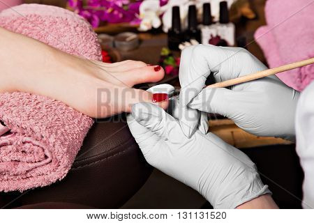 Closeup finger nail care by pedicure specialist in beauty salon. Pedicurist clear cuticle professional scissors for manicure and pedicure.