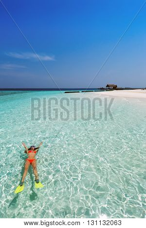 Woman in snorkeling gear floats on the crystal clear waters of the Maldives