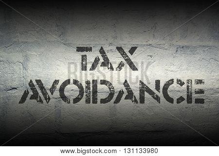 tax avoidance stencil print on the grunge white brick wall