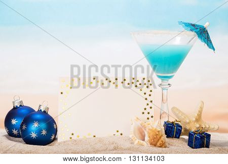 Blank card, cocktail, starfish, shell, Christmas toys and gifts in the sand against the sea.