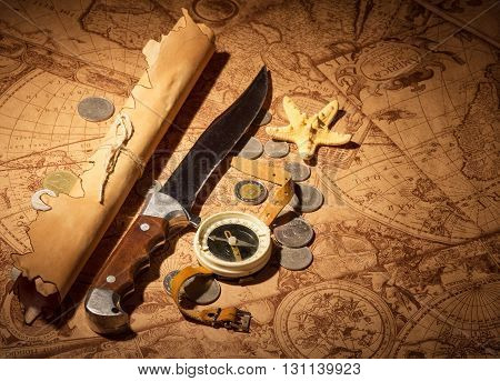 Compass, knife, coin and a starfish on a background of old maps.