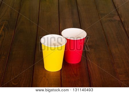 Yellow and red disposable paper cups close up against the dark wood.
