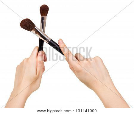 Cosmetic brushes for a make-up in female hands isolated on white background.