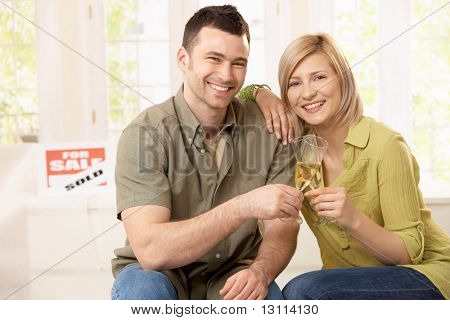 Portrait of happy couple celebrating purchase of new home, laughing at camera.