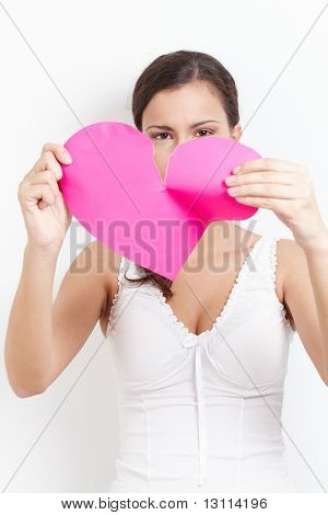 Young lovelorn female tearing paper heart to pieces.?