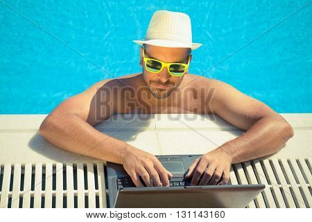 Young guy using his laptop at the edge of swimming pool. He is wearing garish green sunglasses and a hat. Sunny summer day. Working during the summer vacation concept.