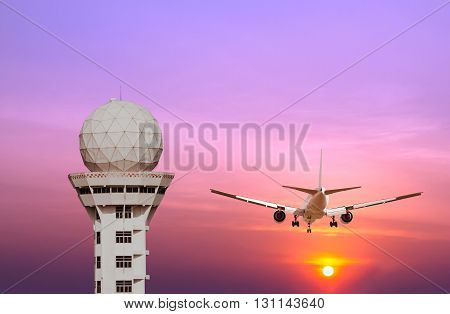 Airport control tower and commercial airplane landing at sunset