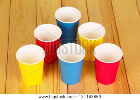 Multi-colored disposable paper cups on the background of light wood.