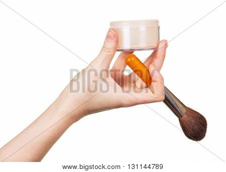 The female hand with a jar of face powder and cosmetic brush isolated on white background.